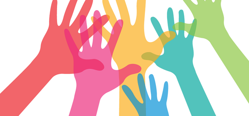 Stock image of multicoloured hands reaching in to join hands